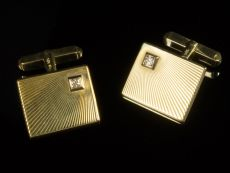A pair of 14k yellow gold cufflings with diamonds